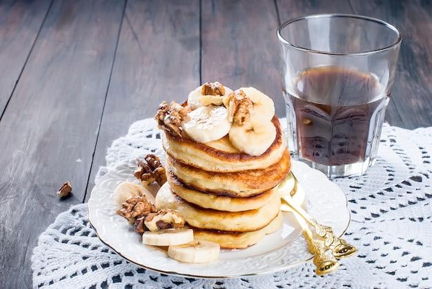 Pannenkoeken met banaan, noten, honing en kopje koffie op donker