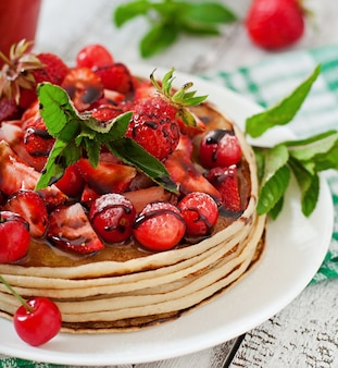 Pannenkoeken met bessen en aardbei smoothie in een rustieke stijl