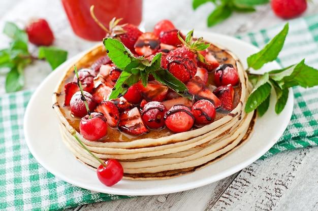Pannenkoeken met bessen en aardbeien smoothie in een rustieke stijl