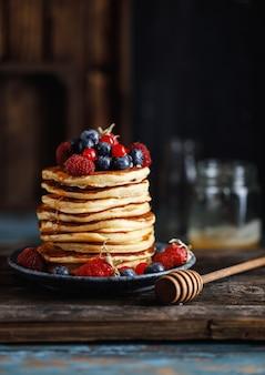 Pannenkoeken met bessen en ahornsiroop. zoete eigengemaakte stapel pannekoeken