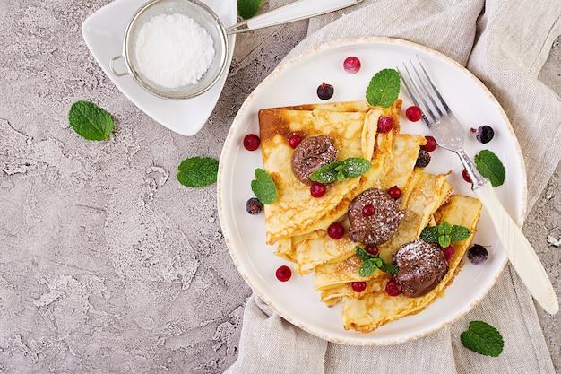 Pannenkoeken met bessen en chocolade versierd met muntblad. lekker ontbijt. bovenaanzicht