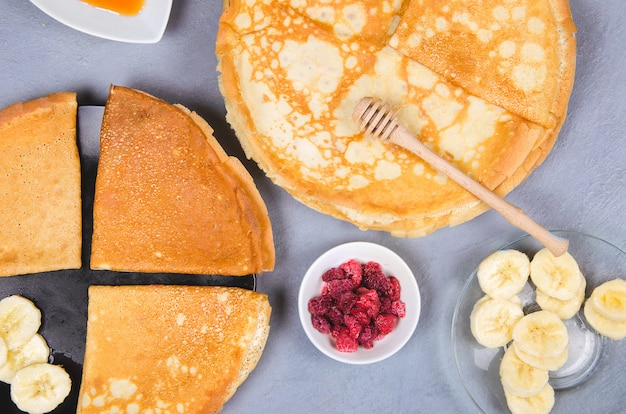 Pannenkoeken met bessen en honing voor het ontbijt op grijze tafel