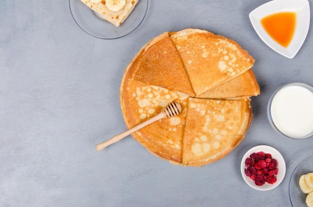 Pannenkoeken met bessen en honing voor het ontbijt op witte grijze tafel