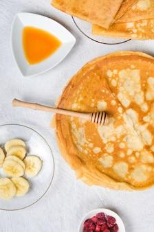Pannenkoeken met bessen en honing voor het ontbijt op witte tafel