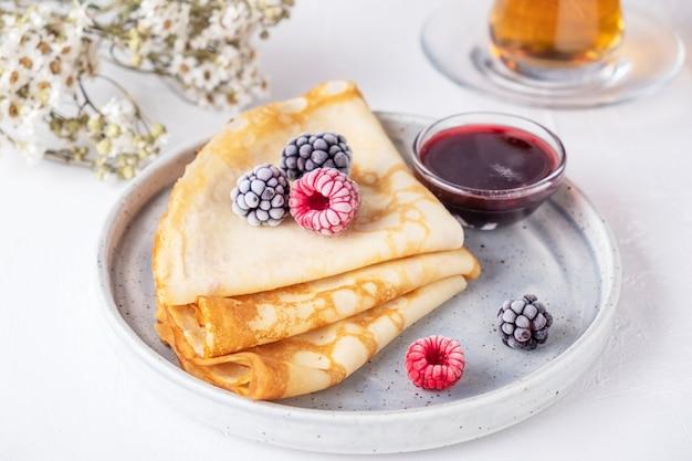 Pannenkoeken met bessen en rode saus op een bord. dunne pannenkoeken met ijsverse bessen.