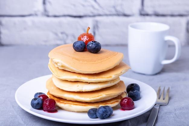 Pannenkoeken met bosbessen, kersen en een mini-appel. een kopje koffie op de achtergrond. traditionele amerikaanse pannenkoeken. detailopname.