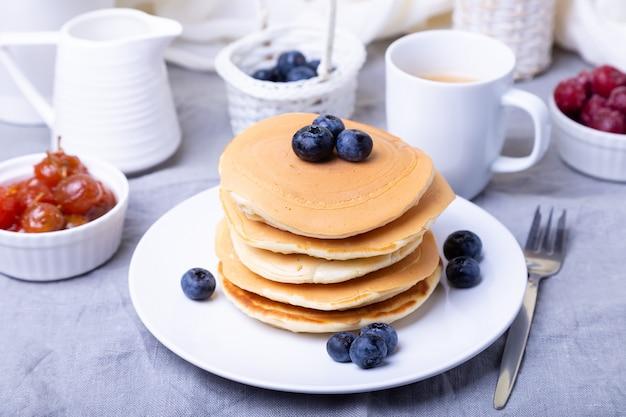 Pannenkoeken met bosbessen, kersen en mini-appeljam. een kopje koffie en juskom op de achtergrond. traditionele amerikaanse pannenkoeken. detailopname.