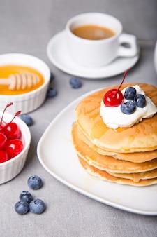 Pannenkoeken met bosbessen, kersen, zure room, honing en koffie.