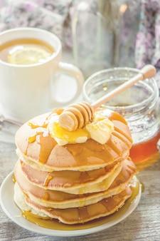 Pannenkoeken met boter en honing en citroenthee voor het ontbijt. selectieve aandacht.