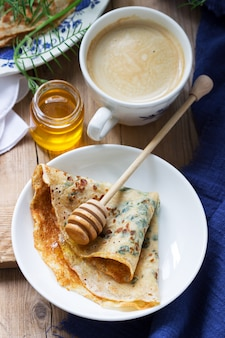 Pannenkoeken met brandnetel en spinazie geserveerd met honing en koffie