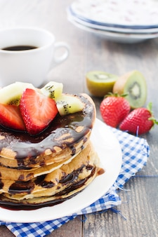 Pannenkoeken met chocolade, aardbeien en kiwi op houten tafel