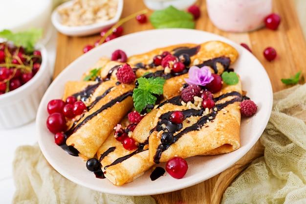 Pannenkoeken met chocolade, honing, noten en zomerbessen. lekker ontbijt