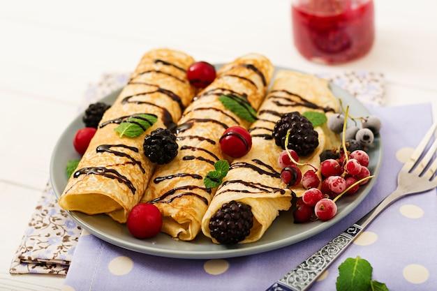 Pannenkoeken met chocolade, jam en bessen. lekker ontbijt.