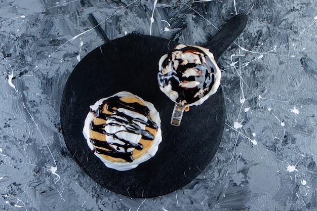 Pannenkoeken met chocolade topping en glas koffie op een houten bord.