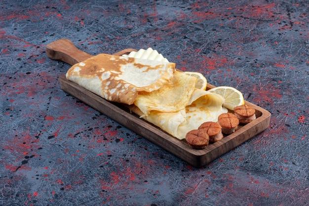 Pannenkoeken met gegrilde worst en schijfjes citroen op een houten schotel.