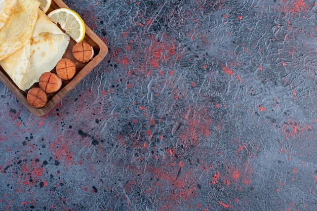 Pannenkoeken met gegrilde worstjes en citroen.