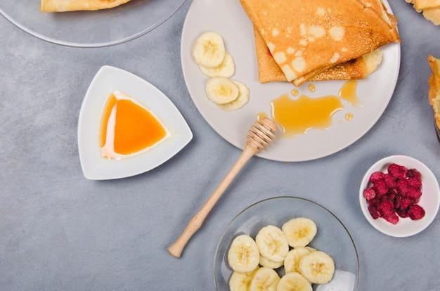 Pannenkoeken met honing als ontbijt op grijze tafel