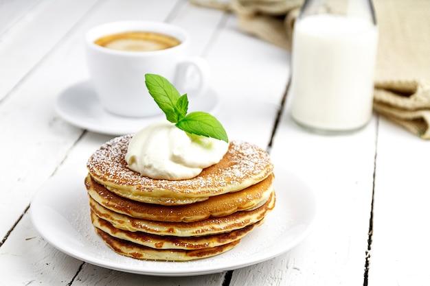 Pannenkoeken met koffie en melk op een tafel gemaakt van witte planken