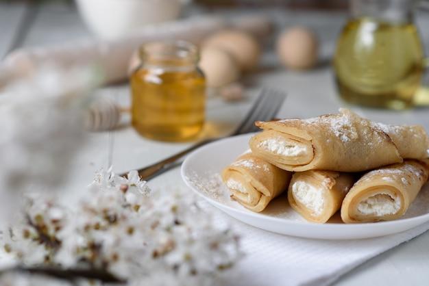 Pannenkoeken met kwark op een witte houten achtergrond. shot met honing, zonnebloempitten, meel en eieren. een traditioneel ontbijt.