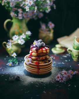 Pannenkoeken met kwark, syrniki, wrongel beignets met bevroren bessen (blackberry) en poedersuiker in een vintage bord. gastronomisch ontbijt