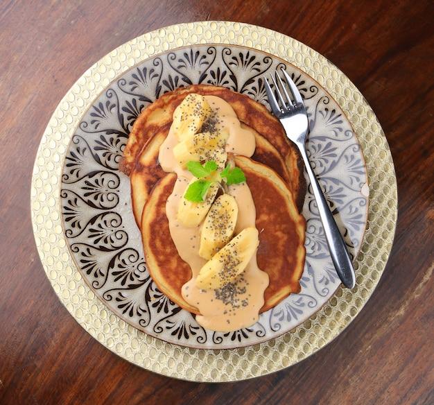 Pannenkoeken met saus, bananen en chiazaadjes geserveerd op een bord met patronen