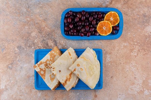 Pannenkoeken met sinaasappel en kersen in een blauwe schotel