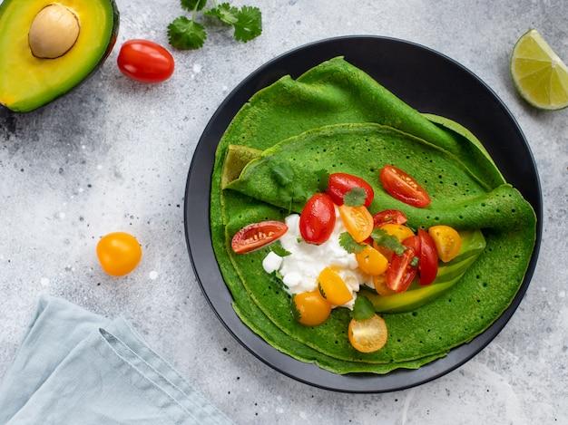 Pannenkoeken met spinazie, avocado, kwark en kleurrijke kerstomaatjes op een donkere plaat. vegetarisch eten. grijs oppervlak. horizontaal beeld.