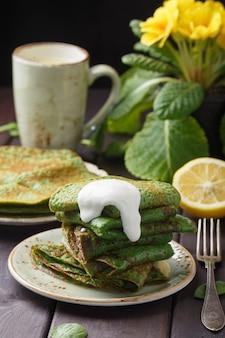 Pannenkoeken met spinazie en zure room op houten tafel.