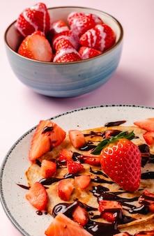 Pannenkoeken met verse aardbeien op een blauwe houten achtergrond
