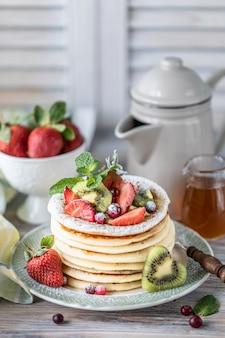 Pannenkoeken met verse bessen van frambozen, krenten, bosbessen, met honing en thee