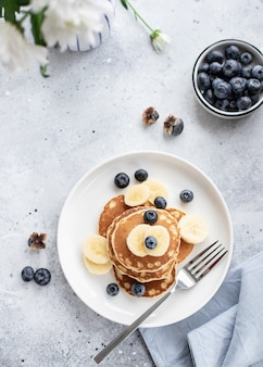 Pannenkoeken met verse bosbessen, banaan op een grijze achtergrond met witte bloemen gezond ontbijt,