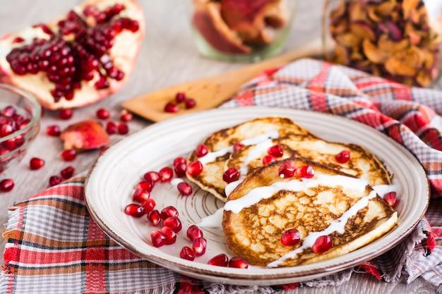Pannenkoeken met zure room en granaatappelzaden op een plaat