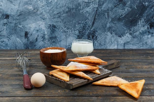 Pannenkoeken op een houten bord met melk en ei