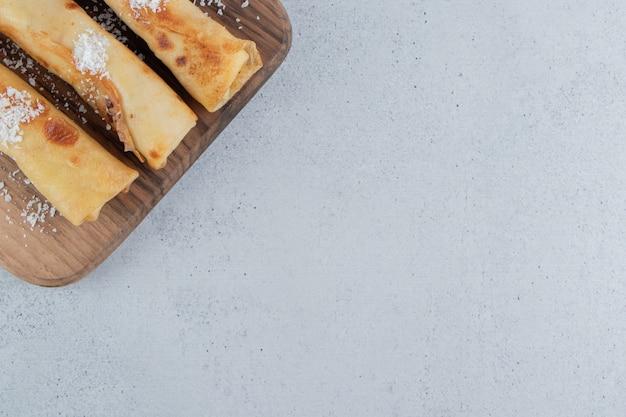 Pannenkoeken op een houten bord op marmeren achtergrond.