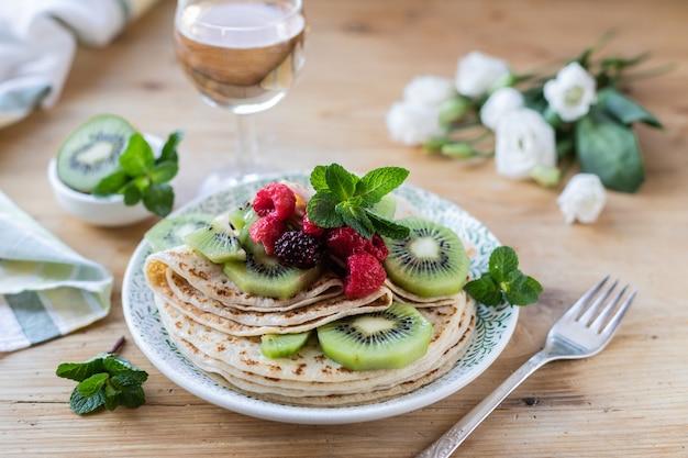 Pannenkoeken op een plaat met bessen op een houten tafel met witte bloemen en vliegende poedersuiker.