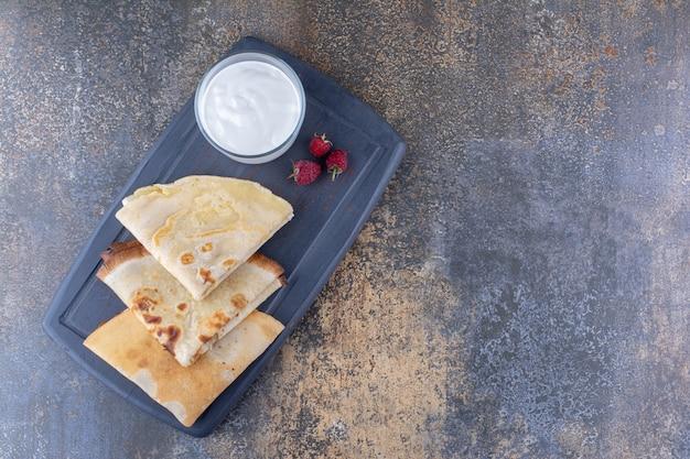 Pannenkoeken op een zwarte schotel met frambozen en een kopje melk