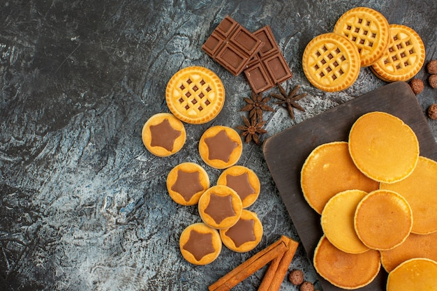 Pannenkoeken op houten schotel met koekjes en snoep op grijze grond