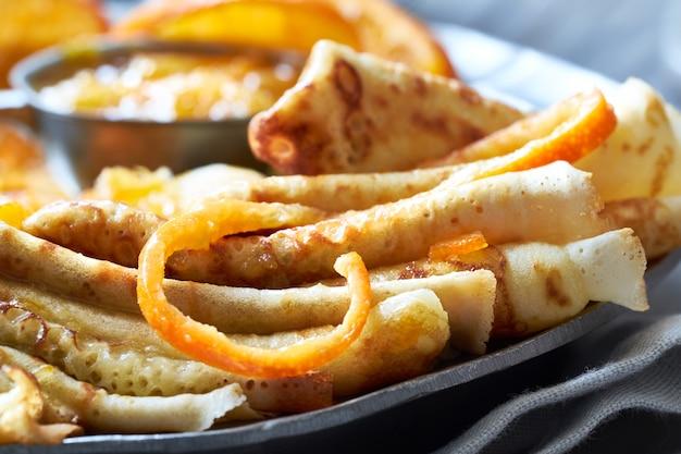 Pannenkoeken suzette, close-up op vintage metalen plaat geserveerd met sinaasappelsaus