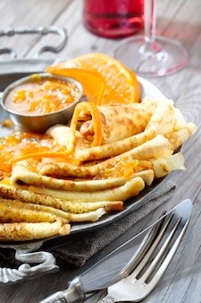 Pannenkoeken suzette op vintage metalen plaat op houten tafel geserveerd met sinaasappelsaus