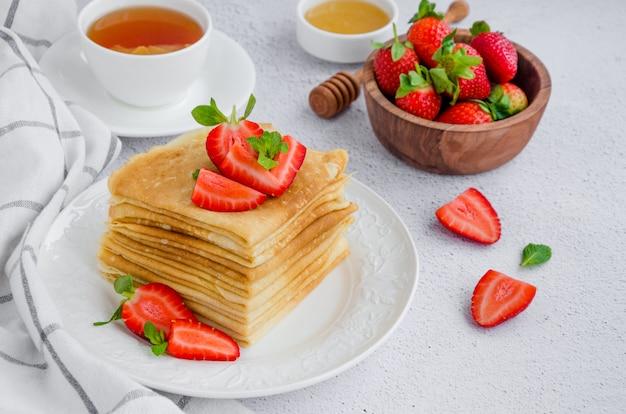 Pannenkoeken, traditionele russische dunne pannenkoeken op een witte plaat met verse aardbeien en honing op een lichte achtergrond.