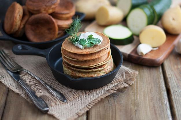 Pannenkoeken van groenten in een gietijzeren koekenpan op een houten achtergrond