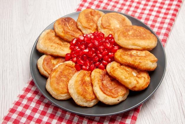 Pannenkoekenbord van zijaanzicht met smakelijke pannenkoeken en granaatappel op het geruite tafelkleed op tafel