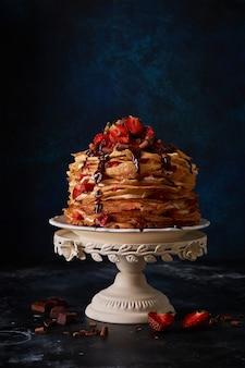 Pannenkoekencake met crêpes met banketbakkersroom, chocoladetopping en bessenaardbeien