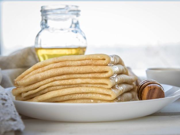 Pannenkoekenhoning en houten honinglepel op een witte plaat