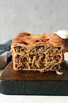 Pannenkoekentaart met vlees en champignons op een grijze achtergrond. pannenkoekencake in de vorm van brood.