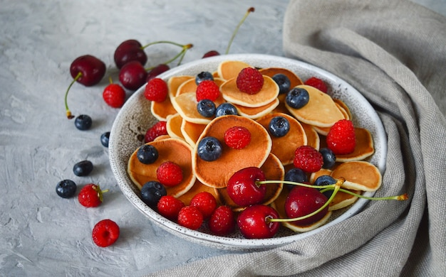 Pannenkoekgranen, minipannenkoekjes in een kom met bosbessen, frambozen, kersen. gezonde voeding. culinaire trend. zelfgemaakt eten.