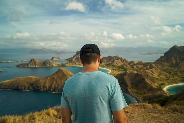 Panorama die van jonge reiziger zich bij de bovenkant van een eiland met een mooi landschap bevinden - padar eiland, indonesië