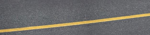 Panorama van asfalttextuur met een lange gele lijn.