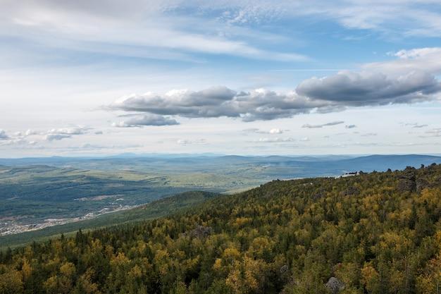 Panorama van bergenscènes in nationaal park kachkanar, rusland, europa. bewolkt weer, dramatische blauwe kleur lucht, ver weg groene bomen