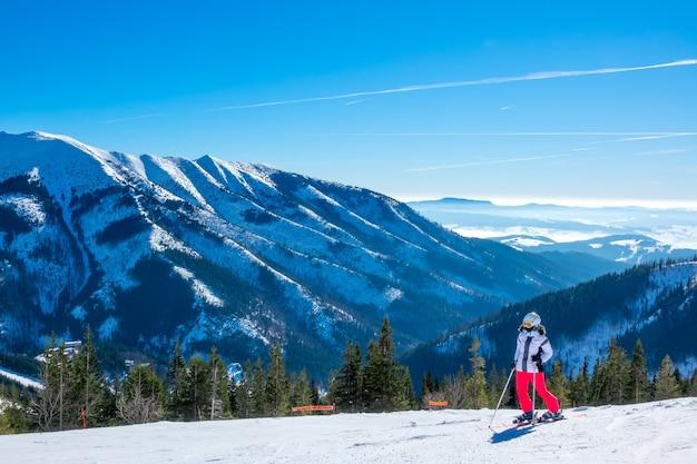 Panorama van besneeuwde bergen in een zonnige winterdag. meisjesskiër stopte en bewondert het uitzicht